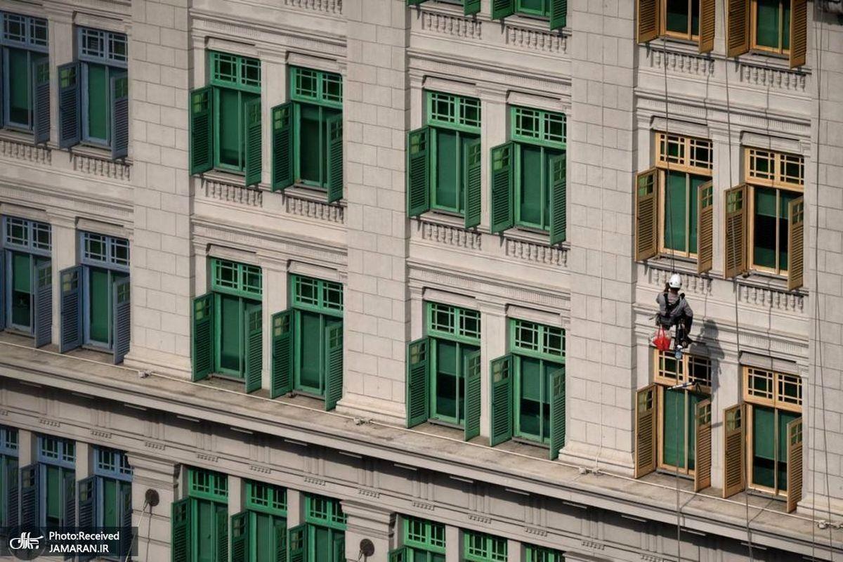 کارگر سنگاپوری در حال تمیز کردن نمای ساختمان +عکس